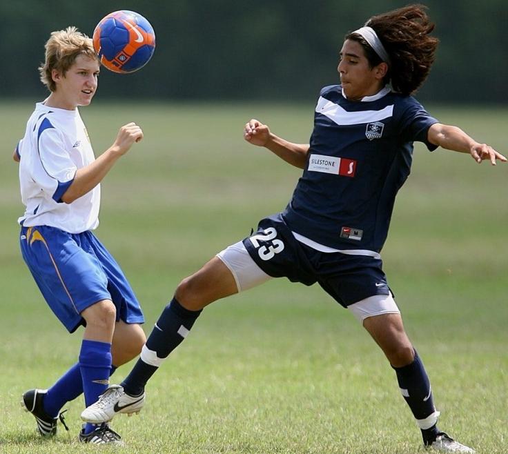 2 niños jugando al futbol