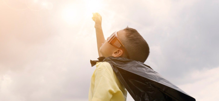 niño mira sol con capa superman