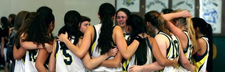 equipo baloncesto abrazado