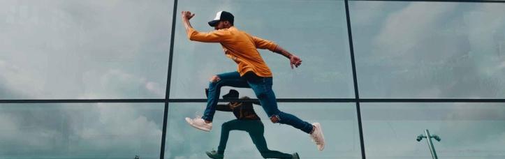 hombre saltando frente a un espejo
